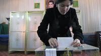 Une femme glisse son bulletin de vote dans un urne, devant un portrait du président turkmène Gourbangouly Berdymoukhammedov, le 15 décembre 2013 à Achkhabad [ / AFP]