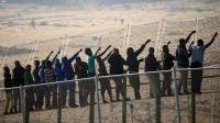 Des immigrants d'origine subsaharienne à la frontière qui sépare le Maroc de l'enclave espagnole de Melilla, le 1er mai 2014 [Blasco de Avellaneda / AFP]