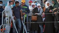Des familles de migrants débarquent d'un navire militaire italien, en Sicile, après avoir été secourus en mer, le 30 juin 2014 [Giovanni Isolino / AFP/Archives]