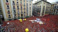 """Une marée humaine célèbre le """"chupinazo"""", le lancement rituel des festivités de la San Fermin devant la mairie de Pampelune, capitale de la Navarre, le 6 juillet 2014  [Rafa Rivas / AFP]"""