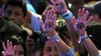 """Des partisans du candidat colombien Juan Manuel Santos célèbrent sa victoire à l'élection présidentielle, le 15 juin 2014 à Bogota montrant la paume de leur mains où est écrit le mot """"paix"""" [Guillermo Legaria / AFP]"""