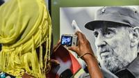 Une femme devant une photo du président cubain Fidel Castro, le 12 août 2014 à La Havane [Adalberto Roque / AFP]