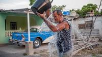 Un cubain se rafraîchit avec un seau d'eau dans une rue de La Havane, le 27 août 2014 alors que le pays est frappé par la canicule  [Yamil Lage / AFP]