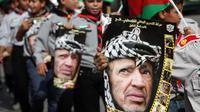 Des jeunes Palestiniens portent des portraits de l'ancien leader Yasser Arafat lors d'une marche célébrant le 9e anniversaire de sa mort, le 11 novembre 2013 à Hebron