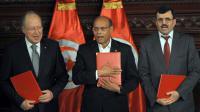 Le chef de l'Etat tunisien Moncef Marzouki (c), le Premier ministre sortant Ali Larayedh (d) et le président de la Constituante, Mustapha Ben Jaafar (g) posent avec des copies de la nouvelle constitution, lors d'une cérémonie à Tunis, le 27 janvier 2014 [Fethi Belaid / AFP]