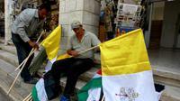Des employés municipaux préparent des drapeaux du Vatican et la Palestine avant l'arrivée du pape François en Terre sainte, le 22 mai 2014 à Bethléem   [Musa Al-Shaer / AFP]