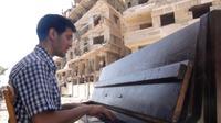 Ayham al-Ahmad joue du piano le 26 juin 2014 au milieu des décombres, dans le camp de réfugiés palestiniens de Yarmouk, au sud de Damas, assiégé depuis un an par l'armée syrienne [Rami al-Sayed / AFP]