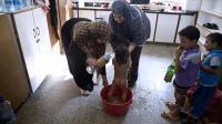 Feriel al-Zaaneen lave sa fille Sama dans une bassine à l'aide de bouteilles d'eau dans une école de l'ONU à Jabalia le 16 août 2014 [Roberto Schmidt / AFP]