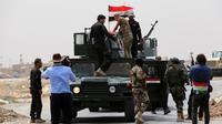 Des membres des forces anti-terroristes irakiennes brandissent le drapeau national, après avoir repris le contrôle d'un point de passage à côté de Badriyah (près de Mossoul), le 19 août 2014 [AHMAD AL-RUBAYE / AFP]