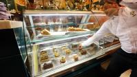 Un employé d'un café sert des pâtisseries à Tripoli le 21 août 2014 [Mahmud Turkia / AFP]