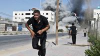 Un Palestinien fuit les frappes israéliens le 23 août 2014 à Gaza [Roberto Schmidt / AFP]