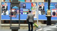 Un homme regarde les affiches électorales des candidats à la présidentielle azerbaïdjanaise, le 7 octobre 2013 à Bakou [Tofik Babayev / AFP/Archives]