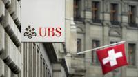 Un drapeau suisse derrière une enseigne de la banque UBS à Bâle [Fabrice Coffrini / AFP/Archives]