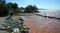 Des femmes empruntent le 29 juillet 2013 le GR2013 qui borde l'étang de Bolmon dont les eaux rouges attestent de la présence de bauxite [ANNE-CHRISTINE POUJOULAT / AFP Photo]