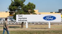 Un homme passe devant le logo du groupe américain Ford, réinstallé à l'entrée du site de Blanquefort (Gironde), le 31 juillet 2013 [Patrick Bernard / AFP]
