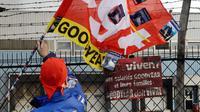 Un salarié agite un drapeau de la CGT devant l'usine Goodyear d'Amiens, le 5 décembre 2013, après l'annonce de la fermeture du site