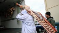 Un employé transporte une pièce de viande sous la surveillance d'un policier, dans un dépôt de boucherie, à Narbonne, le 16 décembre 2013 [Raymond Roig / AFP/Archives]