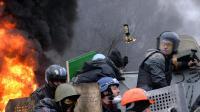 Des manifestants anti-gouvernementaux se protègent de tirs présumés de snipers, le 20 février 2014 à Kiev   [Sergei Supinsky / AFP/Archives]