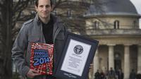 Le perchiste français Renaud Lavillenie, détenteur du record du monde avec 6,16 m, pose avec le livre des records Guinness, le 4 mars 2014 à Paris [Joël Saget / AFP]