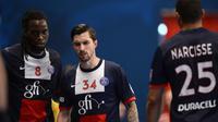 Les joueurs du PSG Handball Ibrahima Diaw (N. 8), Samuel Honrubia (N.34) et Daniel Narcisse (N.25) contre l'équipe de Dunkerque en Division 1 française, le 27 mars 2014 au stade de Coubertin [ / AFP/Archives]
