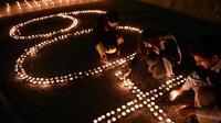 """Des militants du Fonds mondial pour la Nature allument des bougies devant le Parlement pakistanais à Islamabad le 29 mars 2014 à l'occasion de l'opération """"Une heure pour la planète"""" [Farooq Naeem / AFP]"""