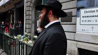 Un Juif devant l'entrée du musée juif de Bruxelles, le 25 mai 2014 où s'amoncellent des gerbes de fleurs, au lendemain de l'attentat qui a fait 3 morts [Georges Gobet  / AFP]
