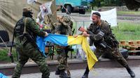 Des miliciens prorusses du bataillon Vostok (Est) déchirent un drapeau ukrainien à Donetsk, le 29 mai 2014 [Viktor Drachev / AFP]