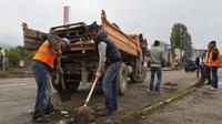 A Mitrovica, des ouvriers retirent une barricade installée il y a trois ans pour empêcher l'accès des Kosovars albanais, le 18 juin 2014 [str / AFP]
