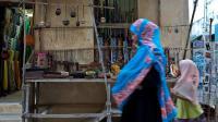 Un mère et sa fille marchent devant une boutique de souvenirs à Lamu au Kenya, le 18 juin 2014 [Ivan Lieman / AFP]