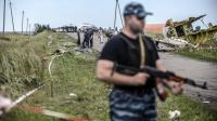 Un séparatiste pro-russe monte la garde devant les décombre de l'avion malaisien le 20 juillet 2014 près de Grabove dans la région de Donetsk [Bulent Kilic / AFP]