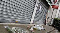 Des fleurs sont déposés devant le tabac où un homme a été tué à Dolomieu le 30 juillet 2014 [Philippe Desmazes / AFP]