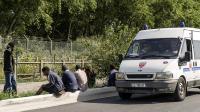 """Un véhicule de CRS passent devant des migrants près de la """"Jungle"""", cette zone de Calais où nombre d'entre eux campent en attendant un passage vers l'Angleterre, le 5 août 2014 [Philippe Huguen / AFP]"""
