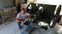 """Eric Marchal, l'un des fondateurs de """"La main de Massiges"""", pose à côté d'un canon dans les tranchées de la Première guerre mondiale [François Nascimbeni / AFP]"""