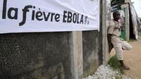 Un homme adossé à un mur près d'une banderole destiné à mobiliser la population dans la lutte contre le virus Ebola, le 10 août 2014 à Abidjan  [Sia Kambou / AFP]