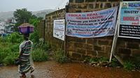 Une femme passe devant des panneaux de sensibilisation à l'épidémie d'Ebola à Freetown, en Sierra Leone, le 13 août 2014 [Carl de Souza / AFP]
