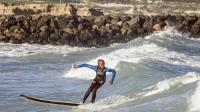 """Un jeune garçon participe le 7 août 2014 sur la plage de Monwabis dans la banlieue du Cap aux activités de Waves for Change (""""des vagues pour changer""""), une ONG fondée par le surfeur britannique Tim Conibear [Rodger Bosch / AFP]"""