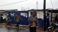Des passants marchent devant une école transformée en centre d'isolement pour les malades d'Ebola d'où se sont enfuis 17 malades à la suite d'une attaque, le 17 août 2014 à Monrovia au Libéria [Zoom Dosso / AFP]