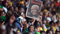 Un portrait de l'ex-président sud-africain, Nelson Mandela, brandi lors de l'hommage organisé à Johannesburg le 10 décembre 2013 [Roberto Schmidt / AFP/Archives]