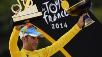 Le vainqueur  du Tour de France, l'Italien Vincenzo Nibali, pose avec ses trophées sur le podium de la 101e édition, le 27 juillet 20104 aux Champs-Elysées à Paris [ / AFP]