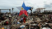 Des rescapés du typhon Haiyan décorent une lanterne géante pour Noël au milieu des ruines à Tacloban le 24 décembre 2013 [Ted Aljibe / AFP]
