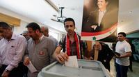 Un Syrien vote le 3 juin 2014 à Damas à l'élection présidentielle, devant une affiche du président sortant Bachar al-Assad, assuré de la victoire [Louai Beshara / AFP]
