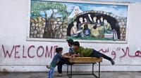 Des enfants palestiniens jouent devant l'école de l'ONU à Gaza City, le 15 août 2014 [Roberto Schmidt / AFP]