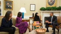 Photo fournie par la Maison Blanche montrant Malala Yousafzai le 12 octobre 2013 entre Michelle et Barack Obama dans le bureau ovale à la Maison Blanche à Washington. A gauche: leur fille Malia [Pete Souza / Maison Blanche/AFP]