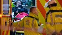 Une femme blessée dans une ambulance devant l'Apollo Theatre de Londres le 19 décembre 2013 [Leon Neal / AFP]