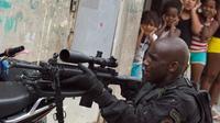Des filles brésiliennes regardent un paramilitaire mener une opération de recherches d'armes dans une favela de Rio le 26 mars 2014 [Christophe Simon / AFP]