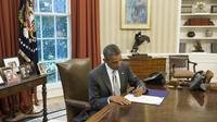 Le président américain Barack Obama signe un document prévoyant l'octroi de 225 millions de dollars supplémentaires à Israël pour le financement du Dôme de fer, le 4 août 2014 à la Maison Blanche [Saul Loeb / AFP]