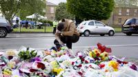 Un homme se recueille le 23 mai 2013 à l'endroit où un soldat a été tué par deux suspects, dans le quartier de Woolwich, à Londres [Justin Tallis / AFP]