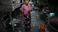 Une femme se tient le 15 octobre 2012 dans une allée du bidonville de Aung Mingalar dans la banlieue de Rangoun [Christophe Archambault / AFP]