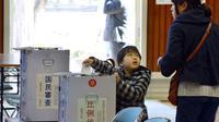 Un enfant dépose dans l'urne le bulletin de sa mère lors des législatives au Japon, le 16 décembre 2012 à Funabashi, près de Tokyo [Tadayuki Yoshikawa / AFP]