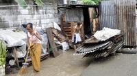 Une Timoraise nettoie devant sa maison inondée le 2 janvier 2013 à Dili [Valentino de Sousa / AFP/Archives]